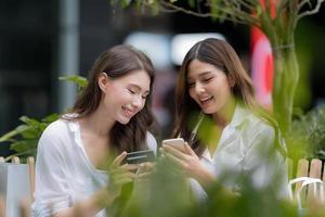 jovem feliz com uma carinha sorridente falando e rindo segurando um cartão de crédito e usando o telefone foto