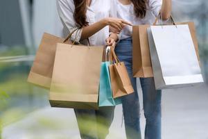 amigos felizes comprando duas mulheres jovens segurando sacolas de compras foto