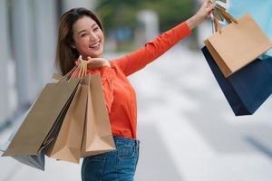 retrato ao ar livre de uma mulher feliz segurando sacolas de compras foto