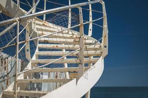 uma escada em espiral branca à beira-mar foto