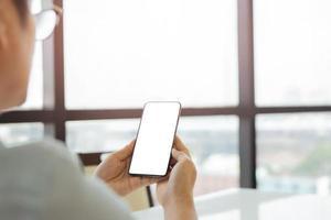 mãos de homem usando telefone inteligente com tela branca em branco foto