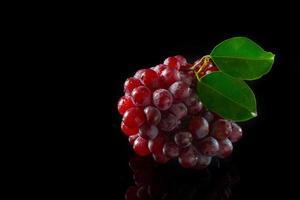 uvas vermelhas em acrílico preto foto