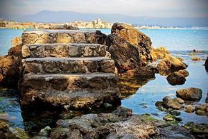 escada de pedra da torre velha isolada no fundo de água do mar azul com pedras e montanhas no horizonte foto