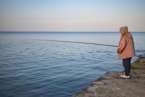 pescador idoso no cais pega peixe foto