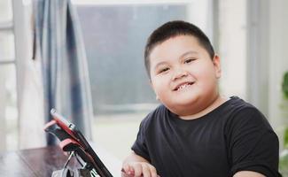 linda criança asiática aprendendo estudo de aula online em um tablet em casa foto