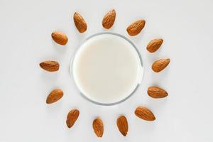 um copo de leite de amêndoa em um fundo branco foto