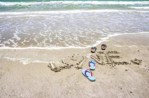 chinelos com amor escritos à mão na praia foto