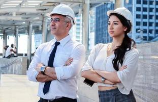 engenheiros inspecionam o local projetos de construção ao ar livre no moderno centro da cidade. engenheiros usam capacetes de segurança brancos para segurança foto