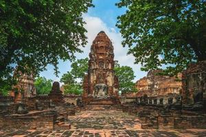 Prang e estátua de Buda em Wat Mahathat em Ayutthaya, Tailândia foto