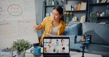 jovem asiática professora de inglês videoconferência ligando no smartphone conversa por webcam aprender ensinar no bate-papo online em casa foto