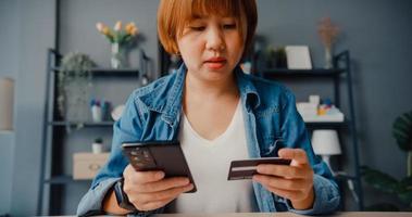 jovem senhora asiática usa um celular para fazer um pedido de compra on-line e pagar contas com cartão de crédito no interior da sala de estar foto