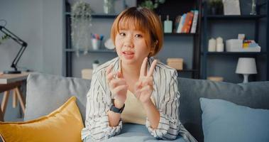 empresária asiática usando laptop fala com colegas sobre plano em videochamada enquanto trabalha em casa na sala de estar foto