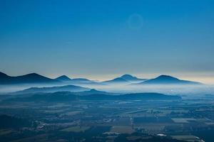 montanhas de nevoeiro no crepúsculo foto