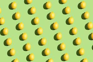 Padrão repetitivo de estilo pop art colorido feito de limões com sombra dura sobre fundo verde foto