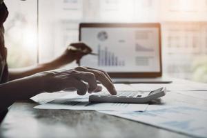empresário usando calculadora para revisar o balanço patrimonial foto