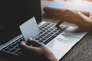 conceito de pagamento online com mão feminina segurando cartão de crédito foto