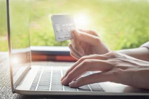 conceito de pagamento online com mulher usando computador e segurando cartão de crédito foto