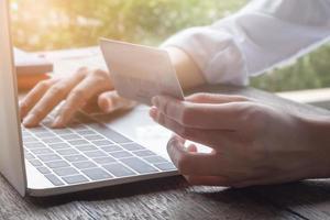 pagamento online com mão feminina segurando cartão de crédito foto