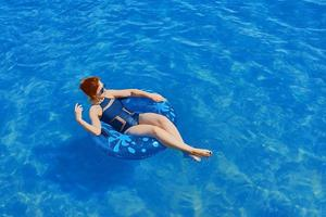 bela jovem relaxando no anel inflável na água do mar foto