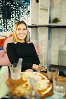 garota incrível sentada em uma cadeira em um café e sorri foto