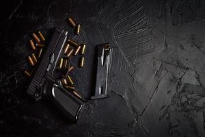 pistola com cartuchos na mesa de concreto preto foto