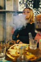 mulher fumando narguilé no café clube foto
