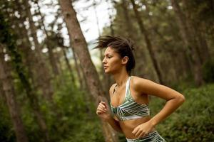 mulher jovem fitness correndo na trilha da floresta foto