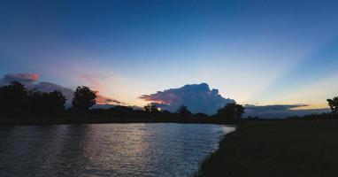 nascer do sol ou pôr do sol com nuvens no rio foto