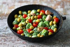 couve-de-bruxelas com legumes e ervas em uma panela foto