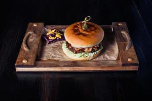 cheeseburguer em uma bandeja de madeira em um restaurante, em um fundo escuro foto