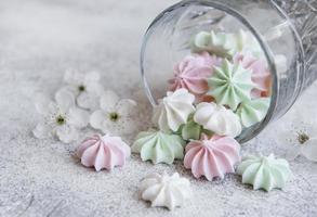 pequenos merengues brancos rosa e verdes no copo foto