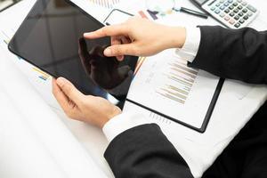 contador asiático trabalhando e analisando relatórios financeiros, projeto de contabilidade com gráfico gráfico e calculadora em um escritório moderno foto