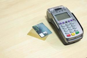 cartão de crédito com terminal de pagamento na mesa de madeira foto