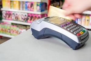 passando a mão o cartão de crédito no terminal de pagamento na loja foto