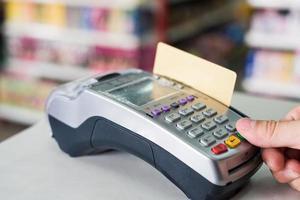 imprensa manual passando o cartão de crédito no terminal de pagamento na loja foto