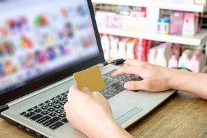 mão segurando um cartão de crédito e usando o laptop para fazer compras online foto