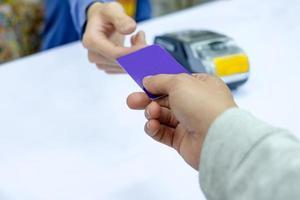 pagamento à mão com cartão de crédito no terminal de pagamento com caixa da equipe foto