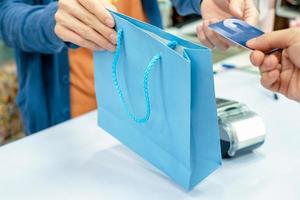 entregando o cartão de crédito em mãos e retirando a sacola de papel do caixa da equipe na loja foto