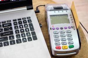 usando cartão de crédito no terminal de pagamento com o laptop na mesa foto