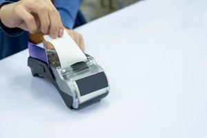 caixa da equipe rasga papel da conta com cartão no terminal de pagamento foto