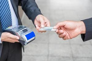 mão segurando o pagamento do cartão de crédito com empresário usando terminal de pagamento foto