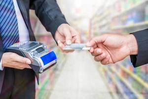 mão segurando o pagamento do cartão de crédito com empresário usando terminal de pagamento em loja de supermercado foto