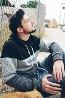 um jovem atraente calmo sentado no chão e uma cerca ao ar livre com os olhos fechados e a cabeça erguida foto