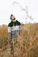 um jovem atraente calmo, com os olhos fechados e a cabeça erguida em um campo amarelo ao ar livre em um dia nublado foto