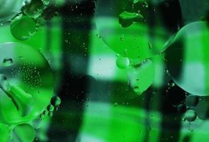 uma macro bonita e colorida de bolhas de óleo na água com uma textura xadrez verde e preta como pano de fundo foto