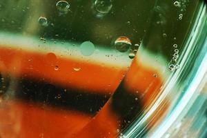 uma macro bonita e colorida de bolhas de óleo na água com uma textura de listra branca, verde e vermelha como padrão de fundo com filtro vintage foto