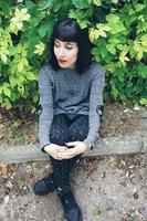 Linda mulher morena caucasiana, sentada no chão em um parque, usando roupas punk ou góticas e cercada por folhas verdes foto