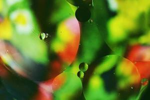 uma macro bonita e colorida de bolhas de óleo na água com uma textura floral verde, vermelha e preta como padrão de fundo com um filtro vintage foto