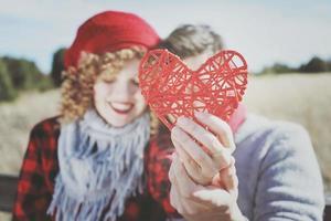lindo close-up de um lindo coração vermelho realizado por um jovem casal romântico apaixonado em um belo bokeh como pano de fundo ao ar livre. lembra amor ou cuidados de saúde foto