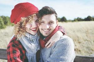 jovem casal de namorados romântico olha para a câmera enquanto sorri e se ama, sentado em um banco de madeira ao ar livre com a natureza como pano de fundo foto